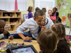 Obama looking through a magnifying glass at students.